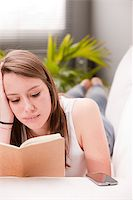girl reading and studying while lying on her sofa in her living room Stock Photo - Royalty-Freenull, Code: 400-07974361