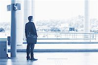 Rear view full body Asian Indian business man waiting bus at public bus station, in blue tone. Stock Photo - Royalty-Freenull, Code: 400-07978345