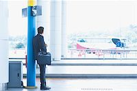 Rear view full body Asian Indian business man waiting bus at public bus station. Stock Photo - Royalty-Freenull, Code: 400-07978346