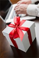 silver box - White Gift Box with Red Ribbon and Bow Near Man Typing on Laptop Computer. Stock Photo - Royalty-Freenull, Code: 400-07982793