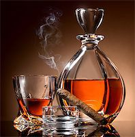 Decanter abd glass of alcohol and cigar on ashtray Stock Photo - Royalty-Freenull, Code: 400-07989442