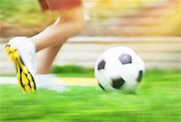 Football game slow motion, body part, sportive teen boy runs for ball, soccerl championship, active teens lifestyle, recreation and hobby Stock Photo - Royalty-Freenull, Code: 400-07989503