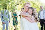 Bride embracing bridesmaid at wedding reception in domestic garden
