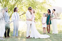preteen kissing - Young couple embracing and kissing during wedding ceremony in domestic garden Stock Photo - Premium Royalty-Freenull, Code: 6113-07992185