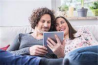 Happy couple using digital tablet, Munich, Bavaria, Germany Stock Photo - Premium Royalty-Freenull, Code: 6121-07992608