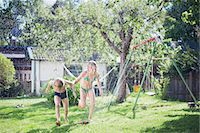 Girl and boy playing with water in garden Stock Photo - Premium Royalty-Freenull, Code: 6102-08001468