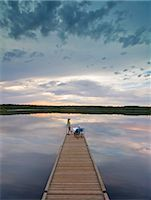 A couple, man and woman sitting at the end of a long wooden dock reaching out into a calm lake, at sunset. Stock Photo - Premium Royalty-Freenull, Code: 6118-08001595