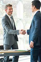 Businessmen shaking hands in office Stock Photo - Premium Royalty-Freenull, Code: 632-08001601