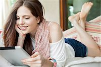 Young woman lying on stomach, looking at digital tablet Stock Photo - Premium Royalty-Freenull, Code: 632-08001793