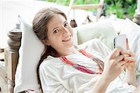 Young woman lying on back with smartphone in hands, portrait Stock Photo - Premium Royalty-Freenull, Code: 632-08001835