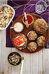 Vegetarian burgers on a platter with side dishes, studio shot
