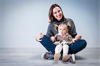 Portrait of mid adult woman sitting on floor with toddler daughter sitting on lap Stock Photo - Premium Royalty-Freenull, Code: 649-08003920