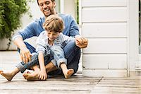 Mid adult man and son laughing and tickling feet on porch Stock Photo - Premium Royalty-Freenull, Code: 649-08004069