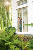 Husband and wife looking out of window into garden Stock Photo - Premium Royalty-Freenull, Code: 649-08004098
