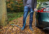 Man charging electric car in forest Stock Photo - Premium Royalty-Freenull, Code: 649-08004126