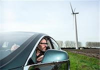 Man in car with wind turbine in background Stock Photo - Premium Royalty-Freenull, Code: 649-08004128