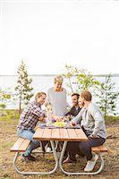 Happy friends having lunch at lakeshore Stock Photo - Premium Royalty-Freenull, Code: 698-08007828