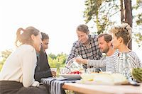 Friends having lunch at picnic table against clear sky Stock Photo - Premium Royalty-Freenull, Code: 698-08007833