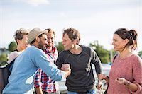 Happy friends greeting each other against sky Stock Photo - Premium Royalty-Freenull, Code: 698-08007844