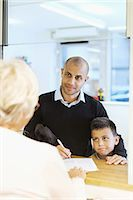 Father and son looking at receptionist while filling forms in orthopedic clinic Stock Photo - Premium Royalty-Freenull, Code: 698-08007888