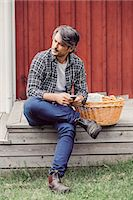Thoughtful farmer with wicker basket holding mobile phone while sitting on porch at yard Stock Photo - Premium Royalty-Freenull, Code: 698-08007952