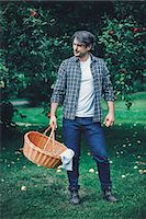 Full length of man carrying wicker basket at apple orchard Stock Photo - Premium Royalty-Freenull, Code: 698-08007954