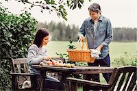 Happy man placing basket on table while woman cutting apples at organic farm Stock Photo - Premium Royalty-Freenull, Code: 698-08007962