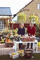 Portrait of happy senior woman cutting fresh apples with man at yard Stock Photo - Premium Royalty-Freenull, Code: 698-08007999