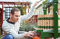 Male farmer collecting fresh apple juice from cider in glass at yard Stock Photo - Premium Royalty-Freenull, Code: 698-08