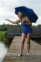 Senior woman in swimwear with umbrella gesturing while standing boardwalk at lake Stock Photo - Premium Royalty-Freenull, Code: 698-08008123