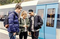 Multi ethnic university students using mobile phone at subway station Stock Photo - Premium Royalty-Freenull, Code: 698-08008125