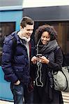 Multi-ethnic couple listening music through mobile phone on subway platform