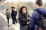 Couple talking on subway platform while friends in background