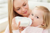 Mother with daughter drinking a bottle of milk. Stock Photo - Premium Royalty-Freenull, Code: 679-08009632