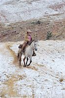 Cowgirl riding horse in snow, Rocky Mountains, Wyoming, USA Stock Photo - Premium Royalty-Freenull, Code: 600-08026173
