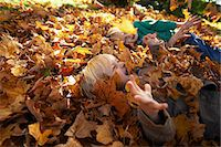 pile leaves playing - Two boys playing in pile of leaves Stock Photo - Premium Royalty-Freenull, Code: 614-08030436