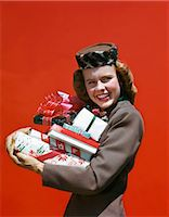 1940s SMILING TEENAGE GIRL CARRYING HOLDING CHRISTMAS PRESENTS LOOKING AT CAMERA Stock Photo - Premium Rights-Managednull, Code: 846-08030416