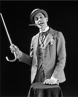 1910s 1920s CHARACTER CON MAN BARKER BOWLER HAT LOUD VAUDEVILLE TYPE CLOTHES POINTING CANE SMOKING CIGAR CONFIDENCE GAME Stock Photo - Premium Rights-Managednull, Code: 846-08030426
