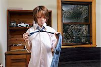 Boy practicing tying large tie in bedroom Stock Photo - Premium Royalty-Freenull, Code: 614-08030624