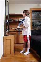 Boy practicing tying large tie in bedroom mirror Stock Photo - Premium Royalty-Freenull, Code: 614-08030625