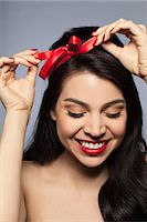 Mid adult woman tying red ribbon in hair Stock Photo - Premium Royalty-Freenull, Code: 614-08030695