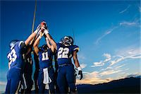 football team - Teenage and young male american football team celebrating and holding up ball Stock Photo - Premium Royalty-Freenull, Code: 614-08030968