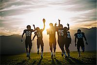 Rear view of teenage and young male american football team celebrating at sunset Stock Photo - Premium Royalty-Freenull, Code: 614-08031108