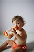A 15 months old baby girl posing with her baby bottle Stock Photo - Premium Rights-Managednull, Code: 877-08031247