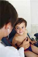 Doctor examining young patient, using stethoscope Stock Photo - Premium Rights-Managednull, Code: 877-08031334