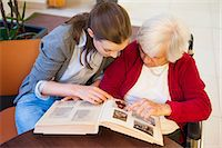 Mid adult woman and her grandmother pointing and looking at photograph album Stock Photo - Premium Royalty-Freenull, Code: 649-08060313