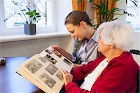 Mid adult woman and her grandmother looking at photograph album Stock Photo - Premium Royalty-Freenull, Code: 649-08060314