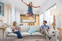 Girl jumping mid air from living room sofa whilst parents use digital tablet Stock Photo - Premium Royalty-Freenull, Code: 649-08060389