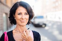 Smiling mature woman with earphones Stock Photo - Premium Royalty-Freenull, Code: 6102-08063136