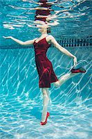 refraction - Mature woman wearing red dress and high heels, standing on one leg, underwater view Stock Photo - Premium Royalty-Freenull, Code: 614-08065888
